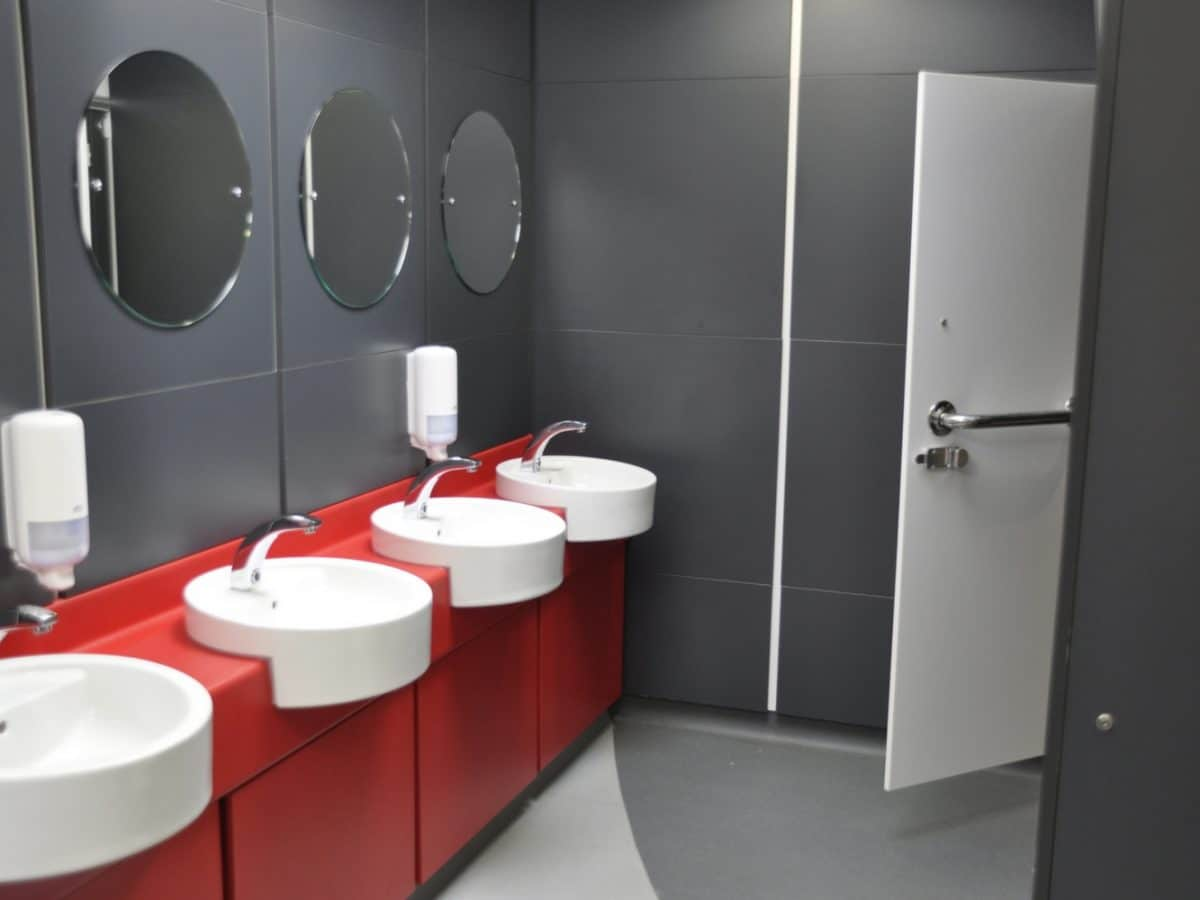 red vanity unit and grey duct panels in college toilet