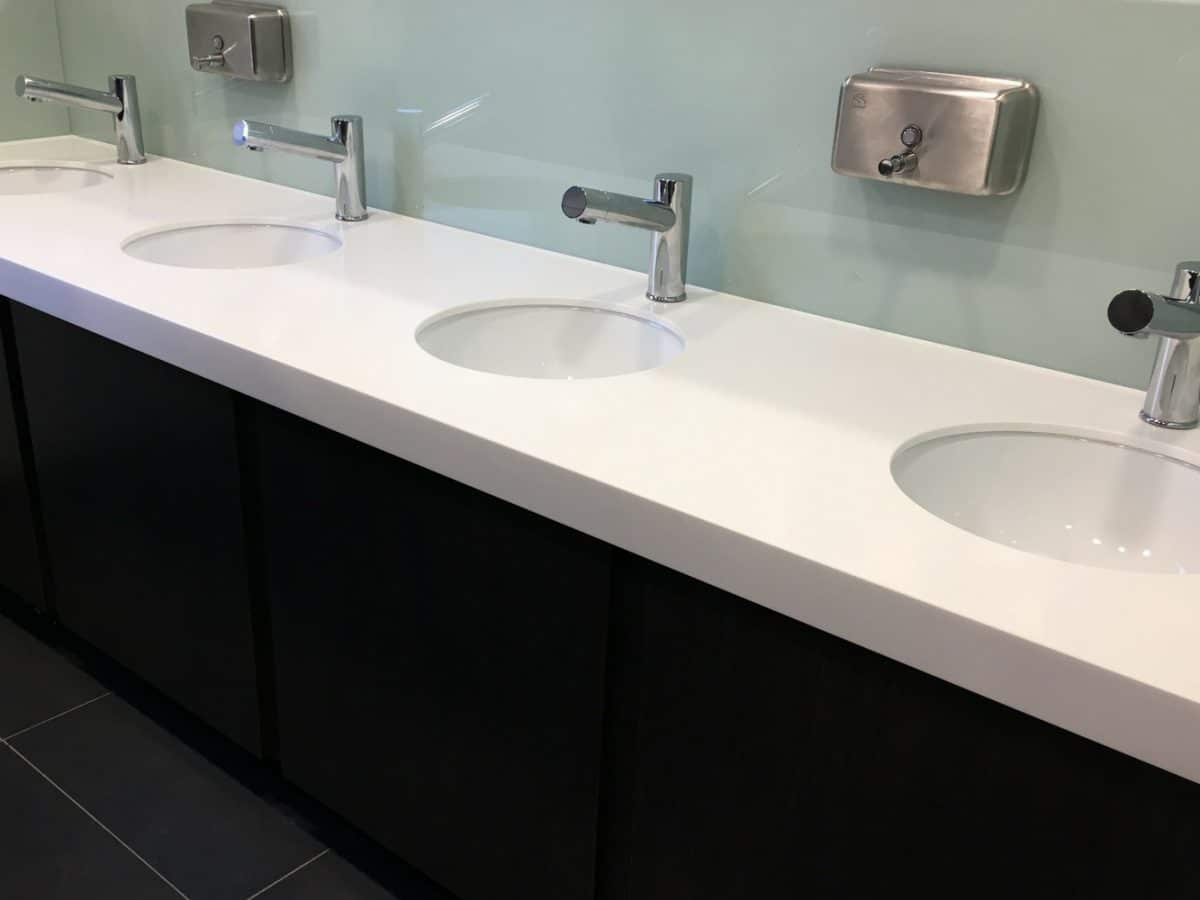 solid surface white vanity unit with black panels