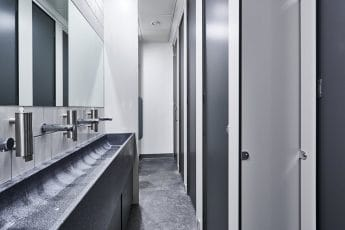 hand wash trough and grey toilet cubicle doors