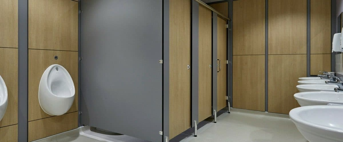 commercial washroom design with wood grain toilet cubicles