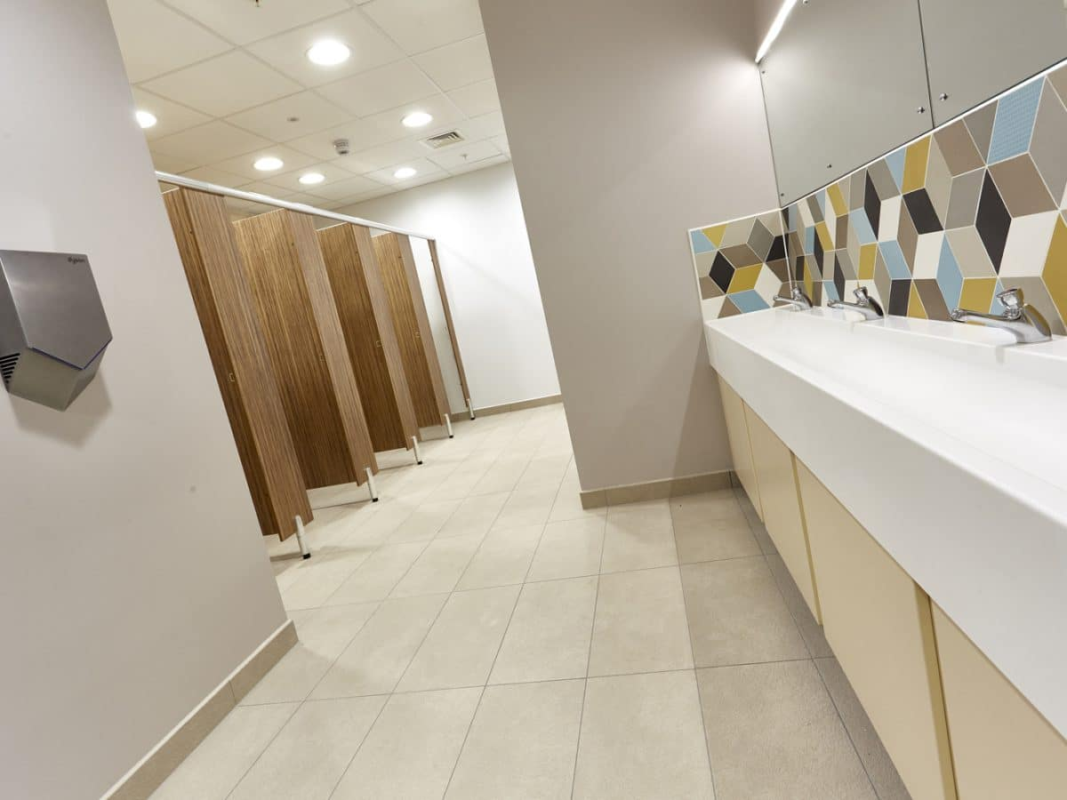 Global Food Producer Toilet Cubicles cream and wood with trough basin slanted