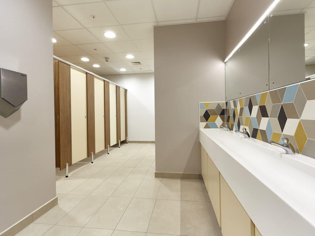 Global Food Producer Toilet Cubicles cream and wood with trough basin